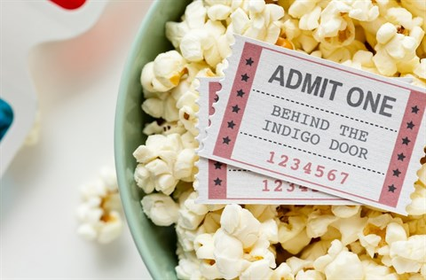 Two entry tickets on top of a green bowl of popcorn with three dimensional glasses in the background