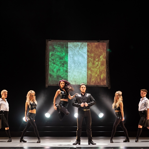 Six dancers on stage in front if the irish flag