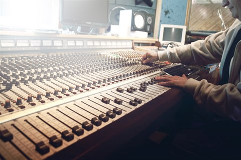 Man using audio mixing desk