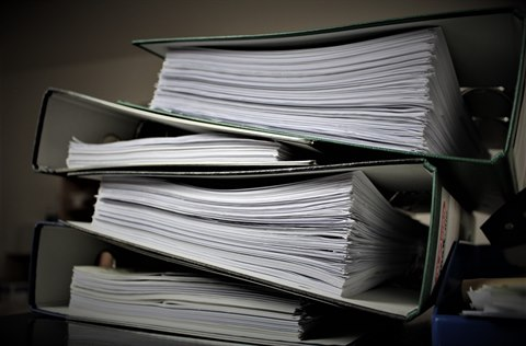 A stack of binders filled with documents