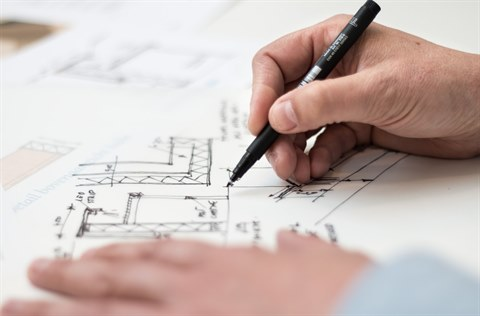 A person sketching blueprints