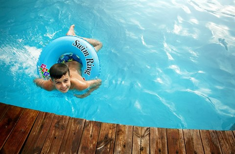 A child floating in a pool with a flotation ring