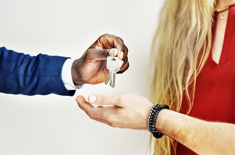 A man hands over a set of keys to a couple