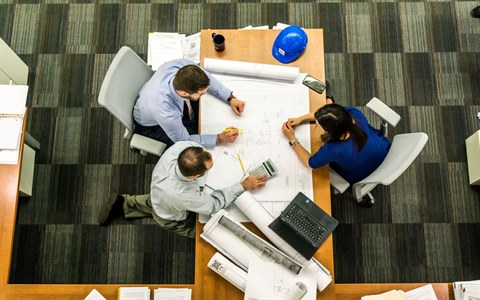 Three people go over planning diagrams at a desk