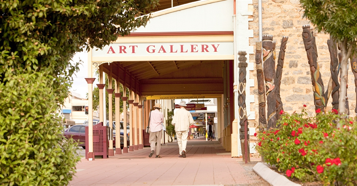 Two people walking along the footpath in front of the Broken Hill Regional Art Gallery.