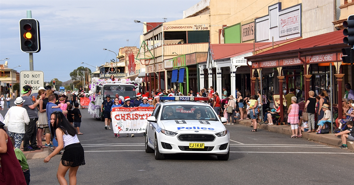 A police car leads the annual Christmas Pageant through Argent street