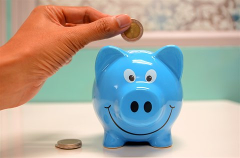 Money going into a blue piggy bank