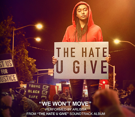Main character standing in crowd with sign saying The hate u give