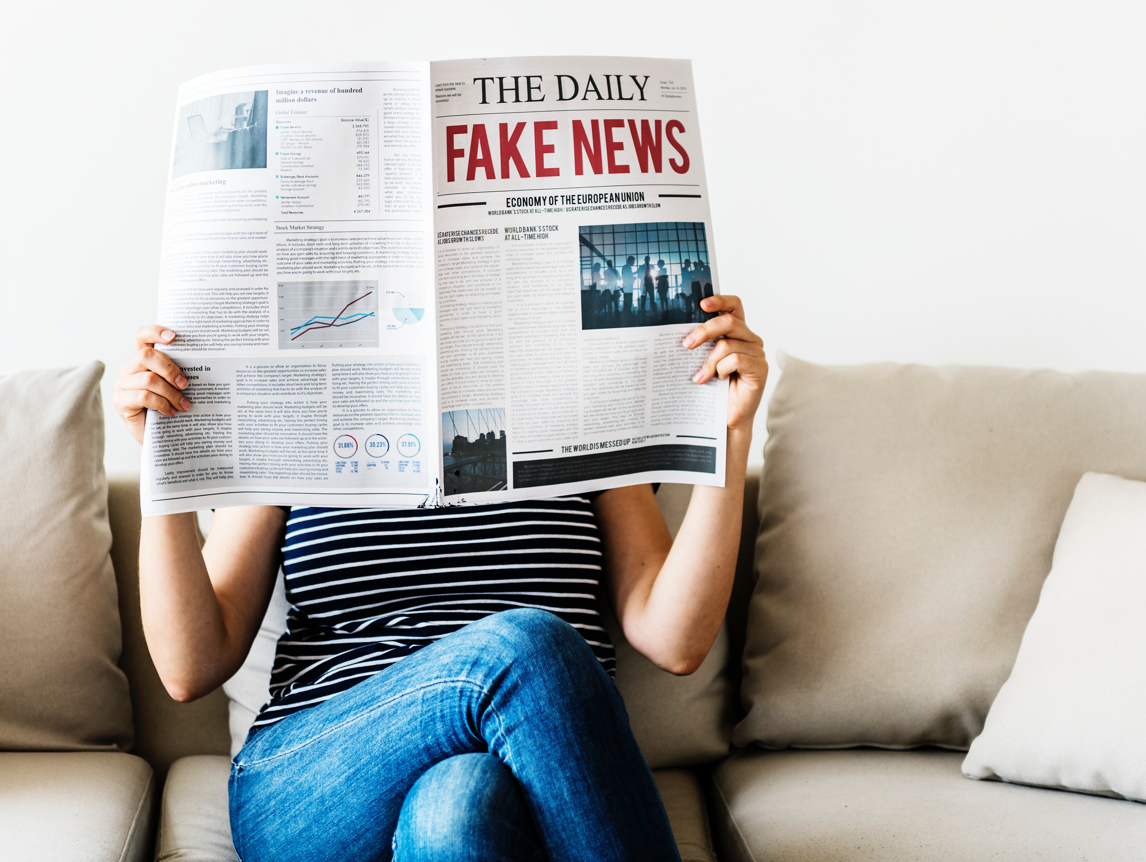 Person reading newspaper with story title Fake news