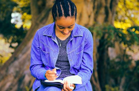 Young woman reading book outside