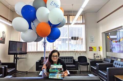 Staff member with books and balloons