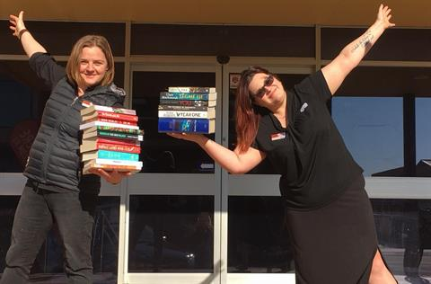 Library staff standing in front of building with books