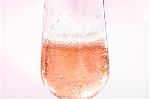 Half full champagne flute with pink background
