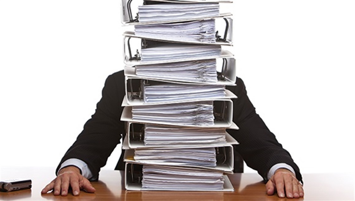 A man sitting at a desk behind a stack of folders