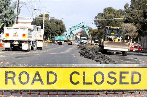 A road closed sign blocks off a road while heavy machinery conducts roadworks